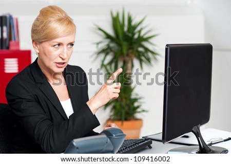 Angry woman in office indicating at computer led screen - stock photo