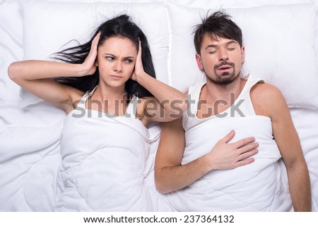 Angry woman is trying to fall asleep while man is snoring.