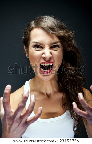 Angry woman on black background - stock photo