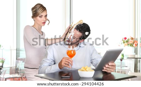 angry woman pulling cake in face to boyfriend cheating - stock photo