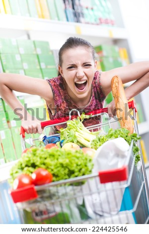 Angry woman pushing a full shopping cart at store with shelves on background. - stock photo