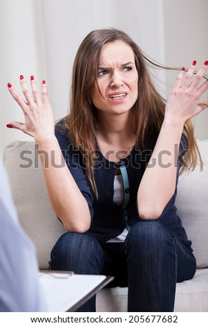 Angry woman talking about her problem on psychotherapy - stock photo