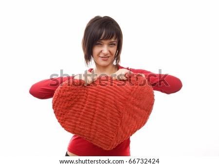Angry woman tearing a heart-shaped pillow - stock photo