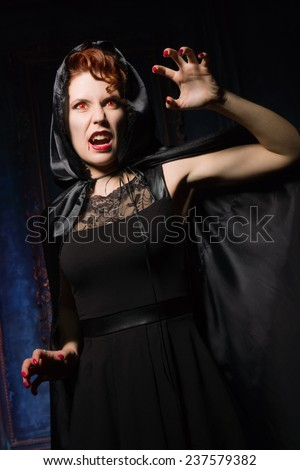 Angry woman vamp in the dark interior