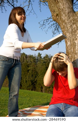 Angry woman wants to break laptop on his head - stock photo