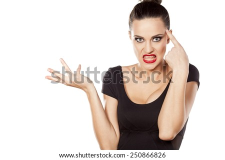 angry woman with a questionable gesture and finger on forehead - stock photo