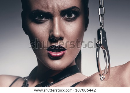 angry woman with handcuffs - stock photo