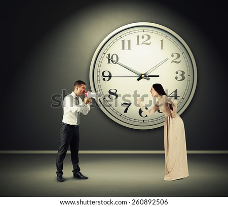 angry yelling woman and screaming man with megaphone in dark room with big clock on the wall - stock photo