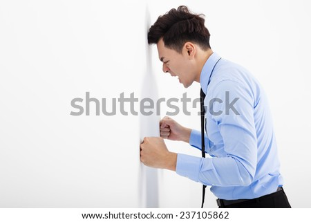 angry young business man  leaning at the wall in office - stock photo