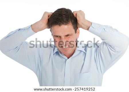 Angry Young Businessman in Light Blue Shirt Pulling his Hair Out While looking at the Camera. Isolated on a White Background.