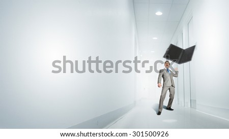 Angry young businessman in rage throwing laptop - stock photo