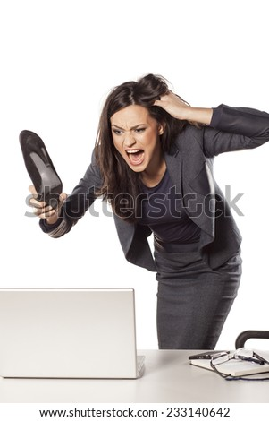 angry young businesswoman attack her laptop with high heels