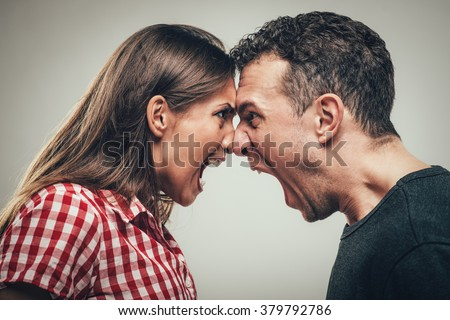 Angry young couple shouting face to face. - stock photo