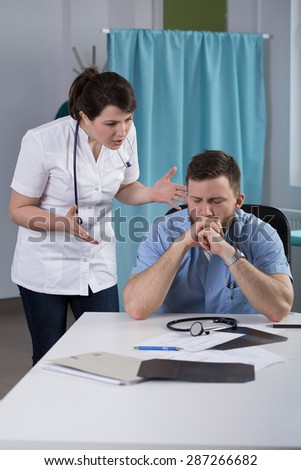 Angry young female doctor yelling at her colleague - stock photo