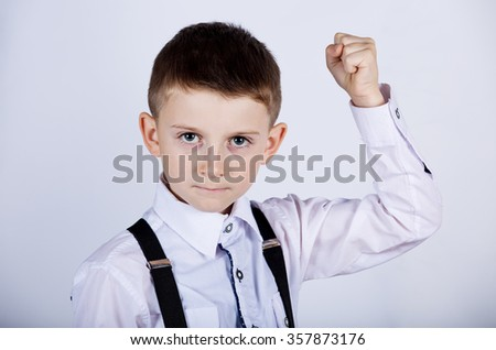 Angry young little boy,child with fists raised in the air.