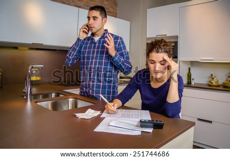 Angry young man arguing at phone while a woman calculating their bank credit lines. Financial family problems concept. - stock photo