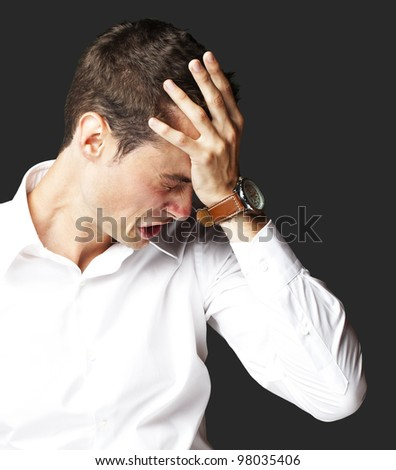 Angry young man doing frustration gesture over black background - stock photo