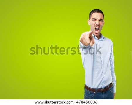 Angry young man pointing on green background