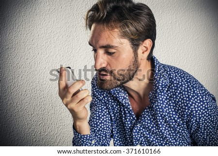 Angry young man screams at the cellular phone - stock photo
