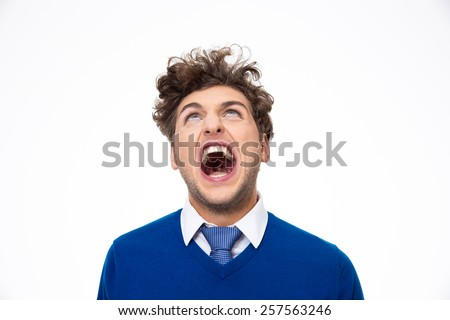Angry young man shouting and looking up at copyspace - stock photo