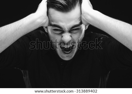 Angry young man, wearing in black shirt, is holding his hands on his head and screaming, on dark studio background, close up - stock photo