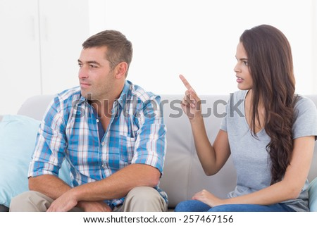 Angry young woman arguing with man while sitting on sofa at home - stock photo