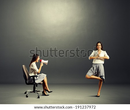 angry young woman screaming at calm woman over dark background - stock photo