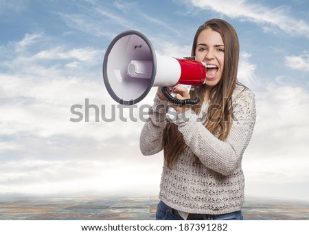 Angry young woman shouting with a megaphone - stock photo
