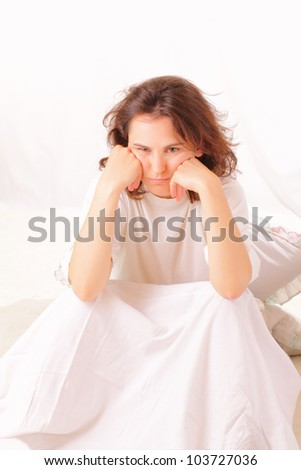 Angry young woman sitting in bed - stock photo