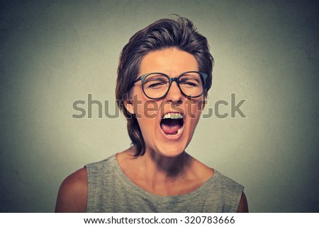 Angry young woman with glasses screaming - stock photo