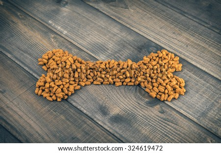 animal bones laid out on wooden background of dry food for dogs and cats photo image - stock photo