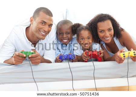 Animated family playing video game lying down on bed at home - stock photo