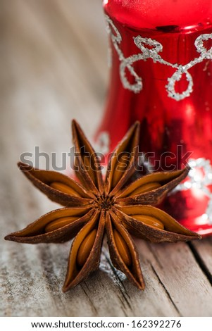 Anise star with bell on wooden background