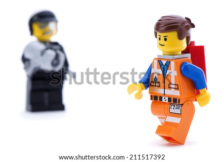 Ankara, Turkey - March 15, 2014 : Studio shot of Lego Movie bad cop trying to catch Emmet isolated on white background.  - stock photo