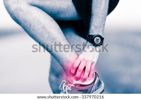 Ankle leg pain, man holding sore and painful foot muscle, sprain or cramp ache filled with red pink bright place. Overtrained injured person when training exercising or running outdoors. - stock photo