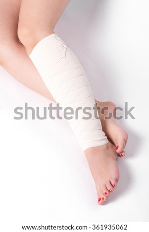 ankle woman on a white background dragged elastic bandage.
