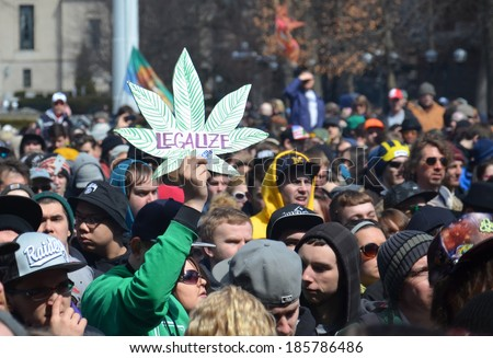 ANN ARBOR, MI - APRIL 5: A participant holds up a sign at the 43rd annual Hash Bash rally in Ann Arbor, MI April 5, 2014. - stock photo