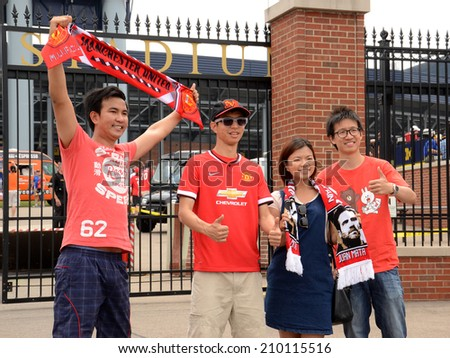 ANN ARBOR, MI - AUGUST 2:  Manchester United fans get their pictures taken outside Michigan Stadium at the International Champions Cup game on August 2, 2014 in Ann Arbor, MI. - stock photo