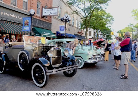 ANN ARBOR, MI - JULY 13: 1928 Ford Model A and 1950 Chevrolet 2d Deluxe at the Rolling Sculpture car show July 13, 2012 in Ann Arbor, MI. - stock photo