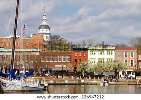 ANNAPOLIS, MARYLAND, USA - APRIL 12, 2013: Tourists shop along the waterfront in historic downtown Annapolis, Maryland, USA, the state capital, dome visible in the background, on April 12, 2013. - stock photo