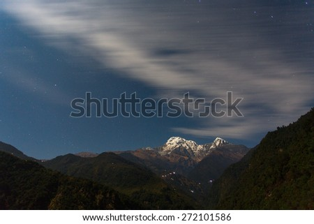 Annapurna I Himalaya Mountains in Nepal at night with clouds moving - stock photo