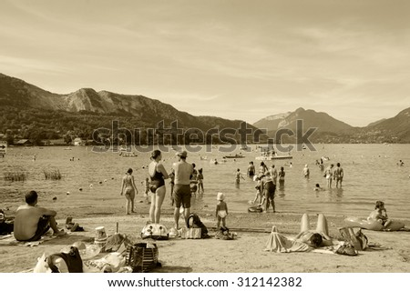 ANNECY LAKE, FRANCE - AUGUST 27, 2015: People relax on the beach of Annecy lake surrounded by beautiful mountains. Annecy Lake is one of most popular French resorts.
