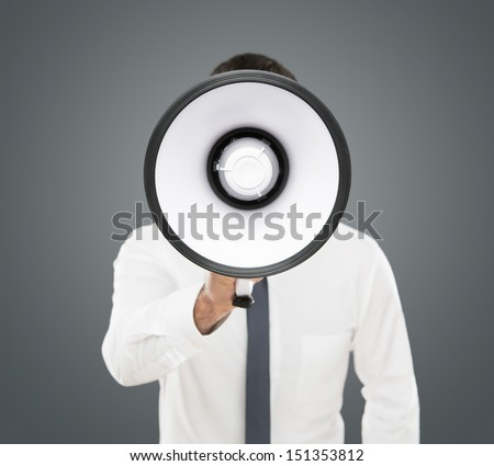 Announcement, young businessman shouting on the megaphone isolated on gray background - stock photo