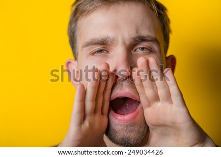 Announcing good news. Handsome young man at camera and shouting while  - stock photo
