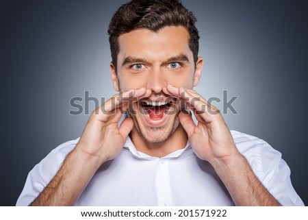 Announcing great news. Happy young man in white shirt shouting while looking at camera and standing against grey background - stock photo