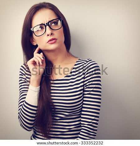 Annoyed angry young woman in eyeglasses thinking and looking up. Vintage closeup portrait - stock photo
