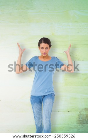 Annoyed brunette gesturing against wooden background in green - stock photo