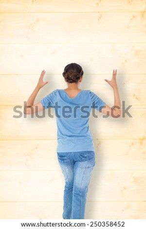 Annoyed brunette gesturing against wooden background in pine - stock photo