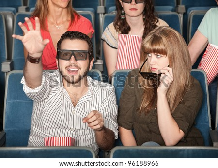 Annoyed girl with date reaching out with 3D glasses - stock photo