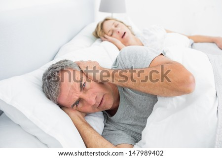 Annoyed man blocking his ears from noise of wife snoring at home in bedroom - stock photo